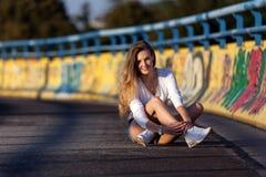 Jeune femme dans les mini-shorts et la chemise blanche Image stock