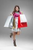 Jeune femme dans les sacs colorés de fixation d'équipement Photos libres de droits