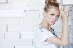 Jeune femme dans les shorts bleus et le T-shirt blanc Images stock