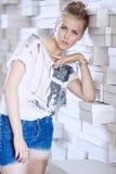 Jeune femme dans les shorts bleus et le T-shirt blanc Photographie stock