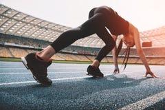 Jeune femme dans les vêtements de sport en position de départ sur le stade courant de voie Photographie stock libre de droits