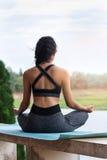 Jeune femme dans les vêtements de sport méditant tout en se reposant dans la pose de lotus Photos stock