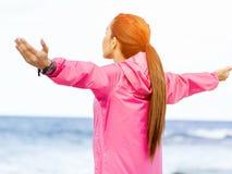 Jeune femme dans les vêtements de sport se tenant au bord de la mer Image libre de droits