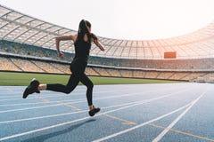 Jeune femme dans les vêtements de sport sprintant sur le stade courant de voie au coucher du soleil Photographie stock