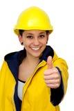 Jeune femme dans les vêtements de travail avec le pouce vers le haut Photographie stock libre de droits