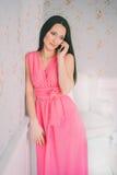 Jeune femme dans parler de téléphone portable de robe de rose Appel de Smartphone Mauvaise nouvelle obtenue cellulaire pensivemen Photo stock