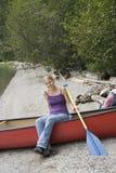 Jeune femme dans un canoë retenant la palette Image libre de droits