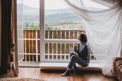 Jeune femme dans un chandail et des jeans d'ami détendant près de la grande fenêtre Photographie stock libre de droits