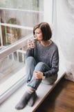 Jeune femme dans un chandail et des jeans d'ami détendant près de la grande fenêtre Images stock
