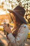 Jeune femme dans un chapeau avec le portrait extérieur de tasse thermo de thermos dans la lumière du jour ensoleillée douce Autom image libre de droits