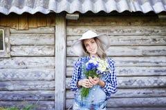 Jeune femme dans un chapeau d'été de paille tenant un bouquet des fleurs Image libre de droits