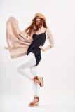 Jeune femme dans un chapeau léger et dans un manteau sur un fond blanc dans la pleine croissance, mode, beauté, style photographie stock libre de droits