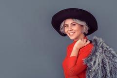 Jeune femme dans un chemisier et un manteau de fourrure rouges d'isolement sur le sourire gris de mur image libre de droits