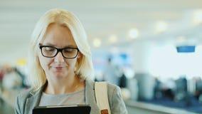 Jeune femme dans un costume et verres dans le grand terminal de l'aéroport Tours sur bande mobile Arrivée dans un nouvel endroit banque de vidéos