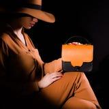 Jeune femme dans un costume reposant et tenant le sac à main en cuir brun et noir sur un fond noir Photos stock