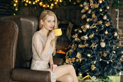 Jeune femme dans un intérieur confortable de Noël Une fille s'assied avec une tasse jaune sous un arbre de Noël parmi beaucoup de photographie stock