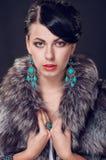Jeune femme dans un manteau de fourrure dans des boucles d'oreille Image stock