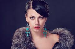 Jeune femme dans un manteau de fourrure dans des boucles d'oreille Photos stock