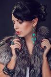 Jeune femme dans un manteau de fourrure dans des boucles d'oreille Images stock