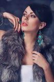 Jeune femme dans un manteau de fourrure dans des boucles d'oreille Image libre de droits