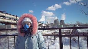 Jeune femme dans un masque protecteur de filtrage sur le fond des tuyaux de tabagisme clips vidéos