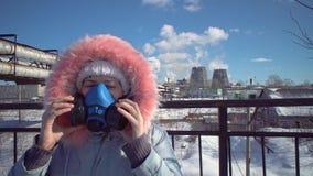 Jeune femme dans un masque protecteur de filtrage sur le fond des tuyaux de tabagisme banque de vidéos