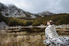Jeune femme dans un poncho et un chapeau appréciant la vue du lac, M Photographie stock