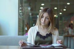 Jeune femme dans un restaurant avec le menu dans des mains Images libres de droits