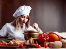 Jeune femme dans un uniforme de chef avec la vieille casserole en laiton et la cuillère en bois photos stock