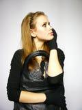 Jeune femme dans une robe avec les gants noirs Images stock