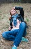 Jeune femme dans une veste noire et des jeans se reposant sur le foin Image stock