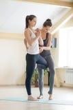 Jeune femme de aide de beau professeur féminin de yogi dans la classe de yoga image stock