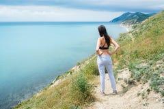 Jeune femme de 25-30 ans de valeur de peine et de regards en mer, vue arrière Photographie stock libre de droits