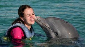 Jeune femme de baiser de dauphin dans l'eau bleue Femme de sourire nageant avec le dauphin banque de vidéos