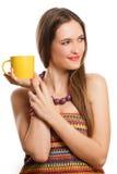 Jeune femme de beauté avec la cuvette jaune de thé Photo stock