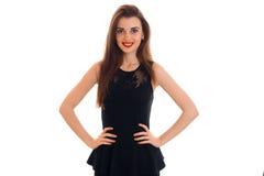 Jeune femme de beauté avec les lèvres rouges dans la robe noire regardant et souriant sur l'appareil-photo d'isolement sur le fon Photo libre de droits