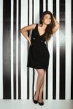 Jeune femme de beauté dans la pose de sourire de robe noire Photographie stock