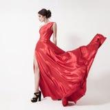 Jeune femme de beauté dans la robe rouge de flottement. Fond blanc. Photographie stock