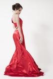 Jeune femme de beauté dans la robe rouge de flottement. Fond blanc. Image stock
