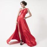 Jeune femme de beauté dans la robe rouge de flottement. Fond blanc. Photo libre de droits
