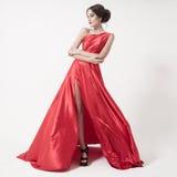 Jeune femme de beauté dans la robe rouge de flottement. Fond blanc. Photos stock