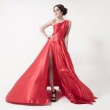 Jeune femme de beauté dans la robe rouge de flottement. Fond blanc. Images stock