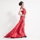 Jeune femme de beauté dans la robe rouge de flottement. Fond blanc. Photos libres de droits