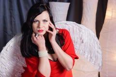 Jeune femme de beauté dans une robe rouge avec les ailes blanches Image stock