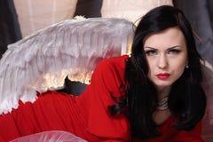 Jeune femme de beauté dans une robe rouge avec les ailes blanches Photos libres de droits