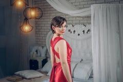 Jeune femme de beauté, femme magnifique dans evebing la robe rouge, vue arrière dans un intérieur chic ou de luxe la fille va à u image libre de droits