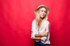 Jeune femme de beauté portant dans le chapeau de paille avec le sourire croisé de mains d'isolement sur le fond rouge images libres de droits