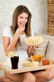 Jeune femme de beauté s'asseyant sur le sofa et ayant le dinn Image stock