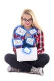 Jeune femme de blondie s'asseyant avec l'ordinateur portable et envoyant l'OIN de messages Photo stock