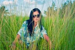 Jeune femme de brune avec des lunettes de soleil sur le champ d'herbe verte images libres de droits